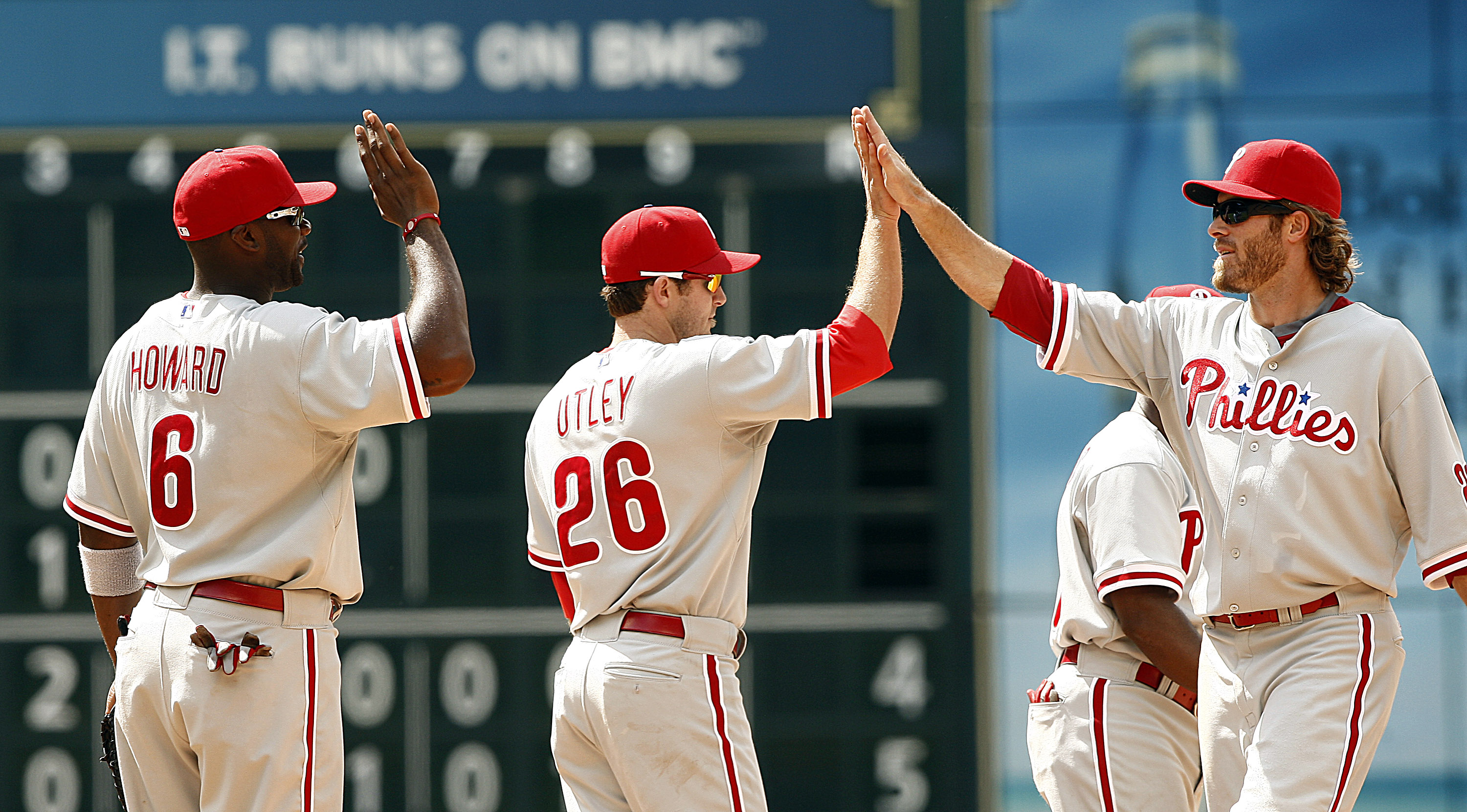 HOUSTON - APRIL 11:  Jayson Werth #28 of the Philadelphia Phillies (R) high fives Chase Utley #26 and Ryan Howard #6 after defeating the Houston Astros 2-1 at Minute Maid Park on April 11, 2010 in Houston, Texas.  (Photo by Bob Levey/Getty Images)