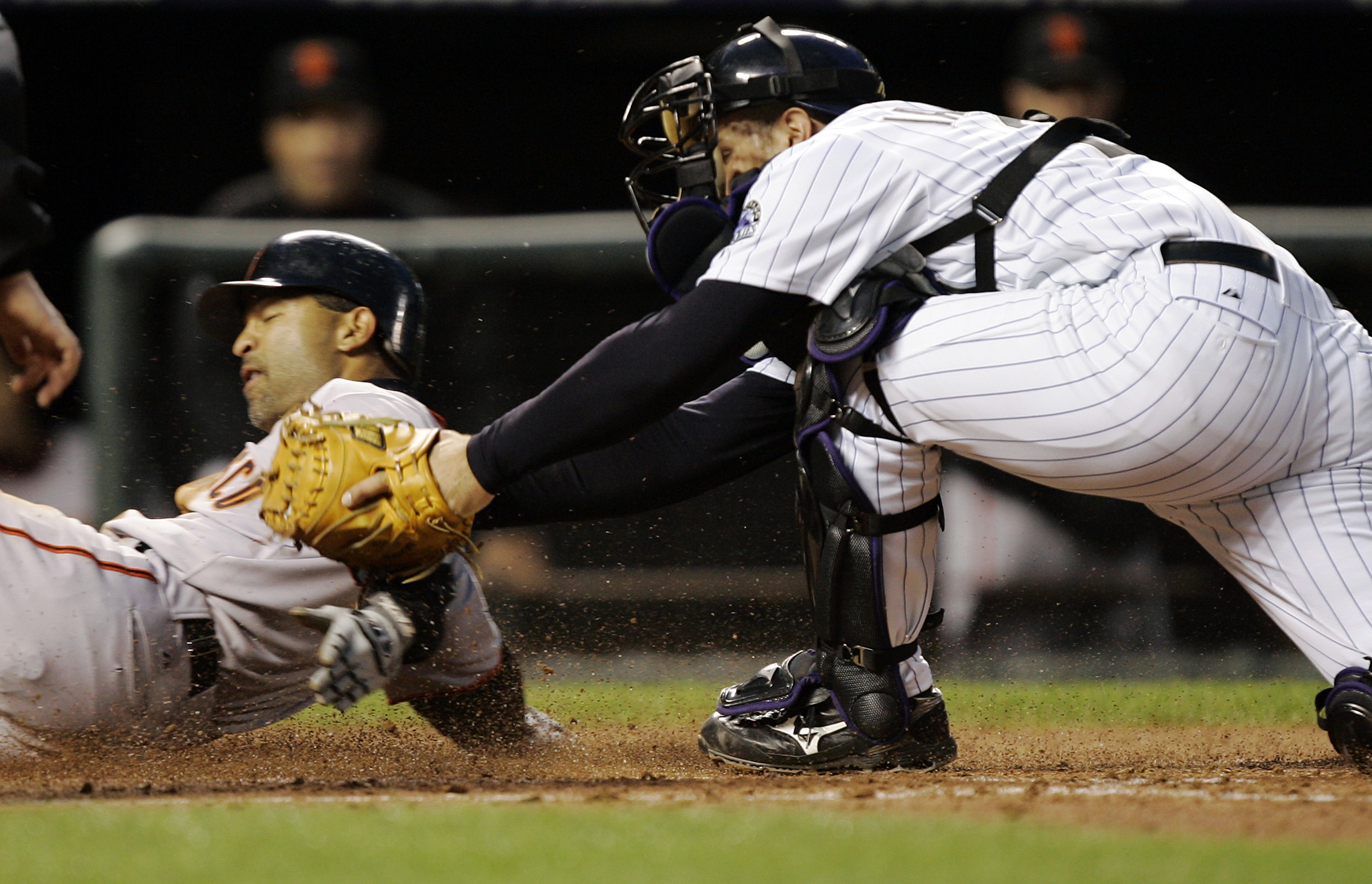 DENVER - APRIL 16:  Dave Roberts #10 of the San Francisco Giants slides safely past catcher Chris Iannetta #20 of the Colorado Rockies on a sacrifice fly by Rich Aurilia in the fourth inning on April 16, 2007 at Coors Field in Denver, Colorado.  (Photo by