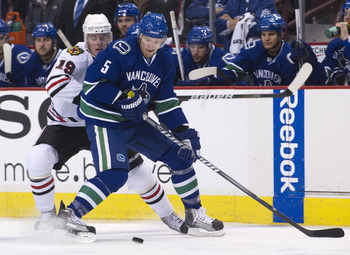 VANCOUVER, CANADA - APRIL 26: Christian Ehrhoff #5 of the Vancouver Canucks and Jonathan Toews #19 of the Chicago Blackhawks battle for the puck during the first period in Game Seven of the Western Conference Quarterfinals during the 2011 NHL Stanley Cup