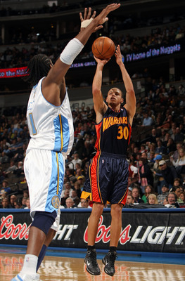 DENVER - JANUARY 05:  Stephen Curry #30 of the Golden State Warriors gets off a shot against Nene #31 of the Denver Nuggets at the Pepsi Center on January 5, 2010 in Denver, Colorado. NOTE TO USER: User expressly acknowledges and agrees that, by downloadi