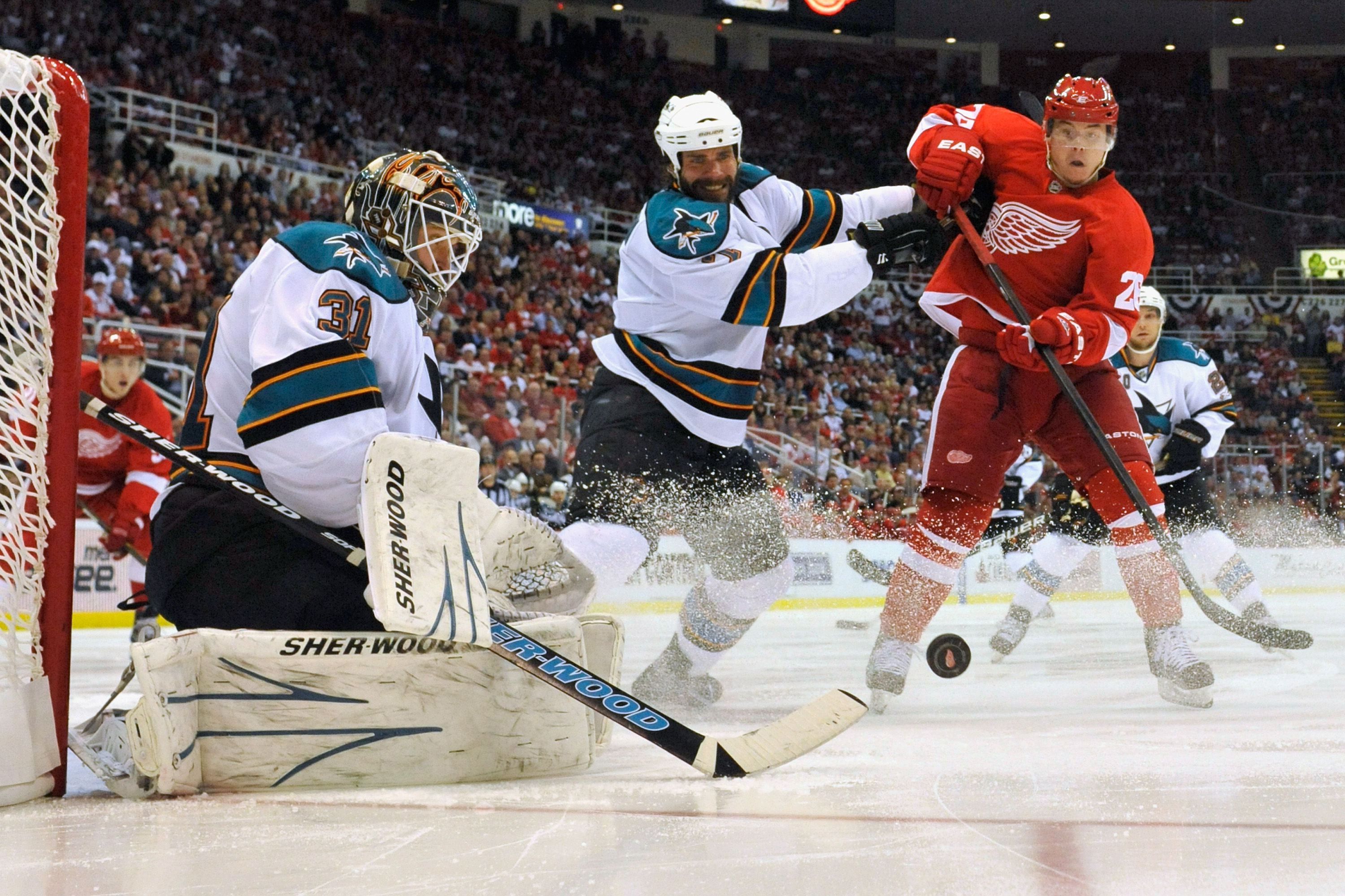 DETROIT - MAY 4:  Goaltender Antti Niemi #31 of the San Jose Sharks makes a save as Niclas Wallin #7 of the San Jose Sharks clears Jiri Hudler #26 of the Detroit Red Wings out of the crease in Game Three of the Western Conference Semifinals during the 201