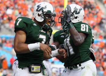 CHARLOTTE, NC - DECEMBER 31:  B.J. Daniels #7 of the USF Bulls celebrates after scoring a touchdown with teammate Dontavia Bogan #81 against the Clemson Tigers during their game at Bank of America Stadium on December 31, 2010 in Charlotte, North Carolina.