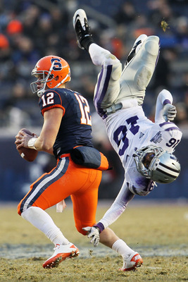 NEW YORK, NY - DECEMBER 30: Quarterback Ryan Nassib #12 of the Syracuse Orange gets around a diving tackle by Terrence Sweeney #16 of the Kansas State Wildcats during the New Era Pinstripe Bowl at Yankee Stadium on December 30, 2010 in New York, New York.