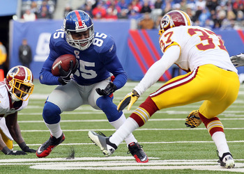 EAST RUTHERFORD, NJ - DECEMBER 05:  Derek Hagan #85 of the New York Giants runs the ball against Reed Doughty #37 of the Washington Redskins on December 5, 2010 at the New Meadowlands Stadium in East Rutherford, New Jersey.  (Photo by Jim McIsaac/Getty Im