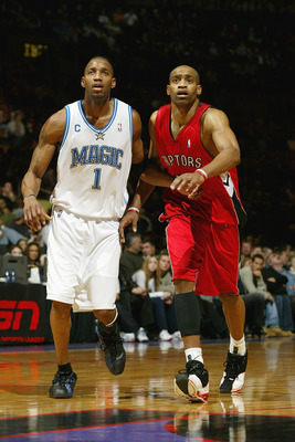 TORONTO - DECEMBER 21:  Tracy McGrady #1 of the Orlando Magic stands next to Vince Carter #15 of the Toronto Raptors during the game on December 21, 2003 at the Air Canada Centre in Toronto, Canada.  McGrady and Carter are cousins. The Magic won 104-93.