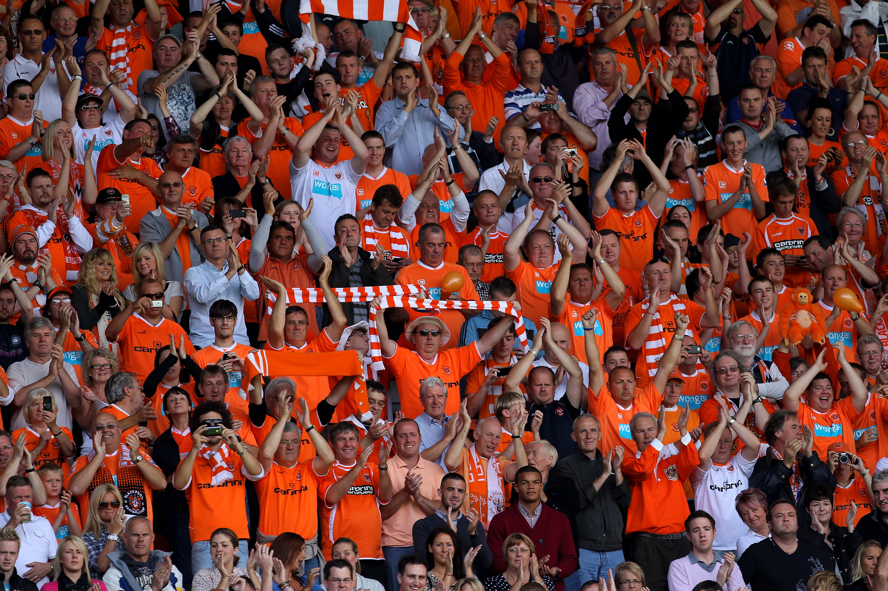 WIGAN, ENGLAND - AUGUST 14:  Blackpool fans show their support during the Barclays Premier League match between Wigan Athletic and Blackpool at the DW Stadium on August 14, 2010 in Wigan, England.  (Photo by Alex Livesey/Getty Images)