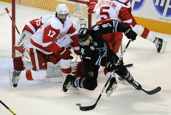 SAN JOSE, CA - MAY 12: Joe Pavelski #8 of the San Jose Sharks tries to get a backhand shot past Patrick Eaves #17 and Jimmy Howard #35 the Detroit Red Wings in Game Seven of the Western Conference Semifinals  during the 2011 NHL Stanley Cup Playoffs at th
