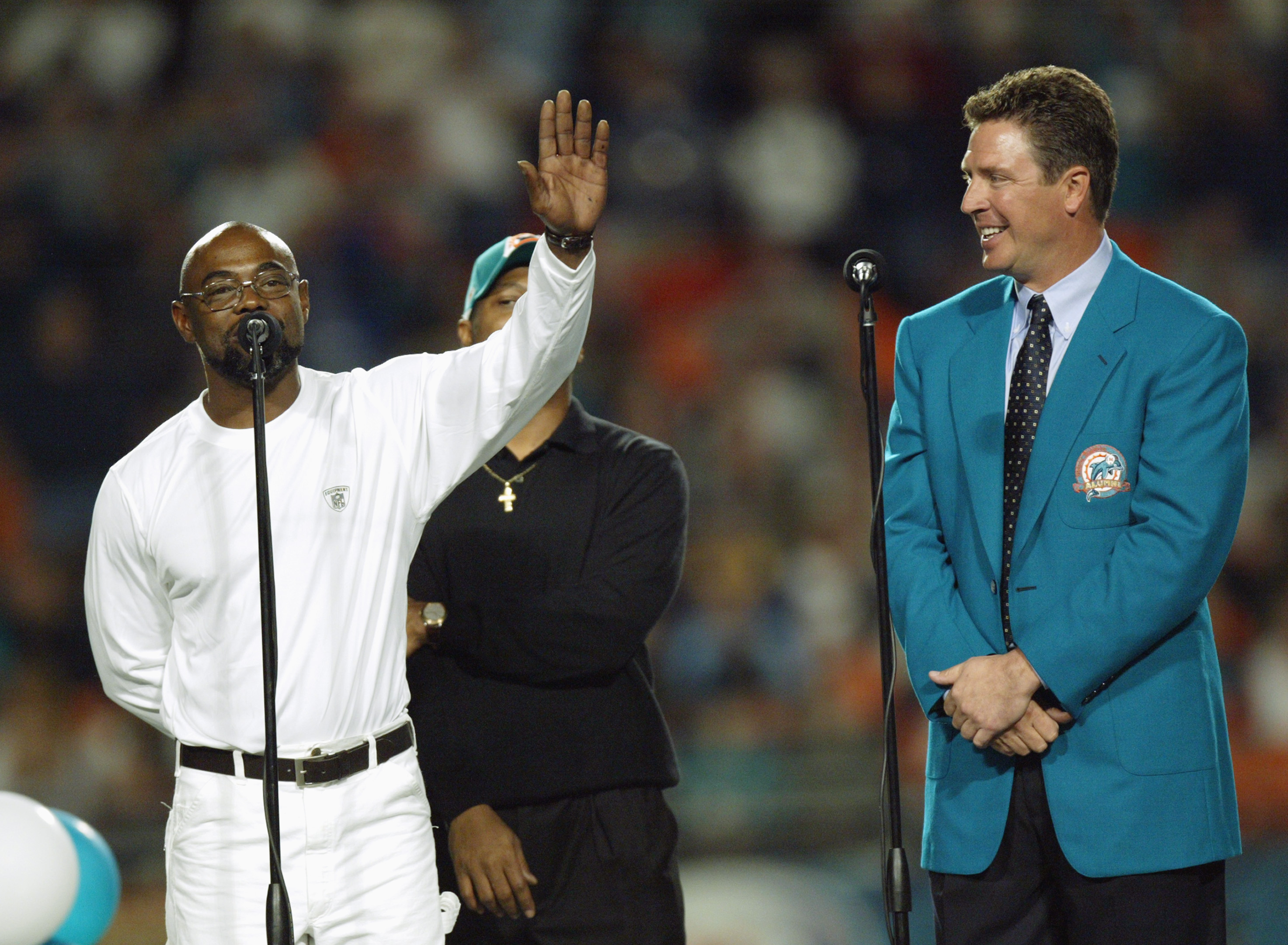 MIAMI - DECEMBER 15:  Former Miami Dolphins player Mark Duper speaks while waving to the crowd as former quarterback Dan Marino watches after Duper and teammate Mark Clayton, obscured were inducted into the Miami Dolphins Hall of Fame during half time of