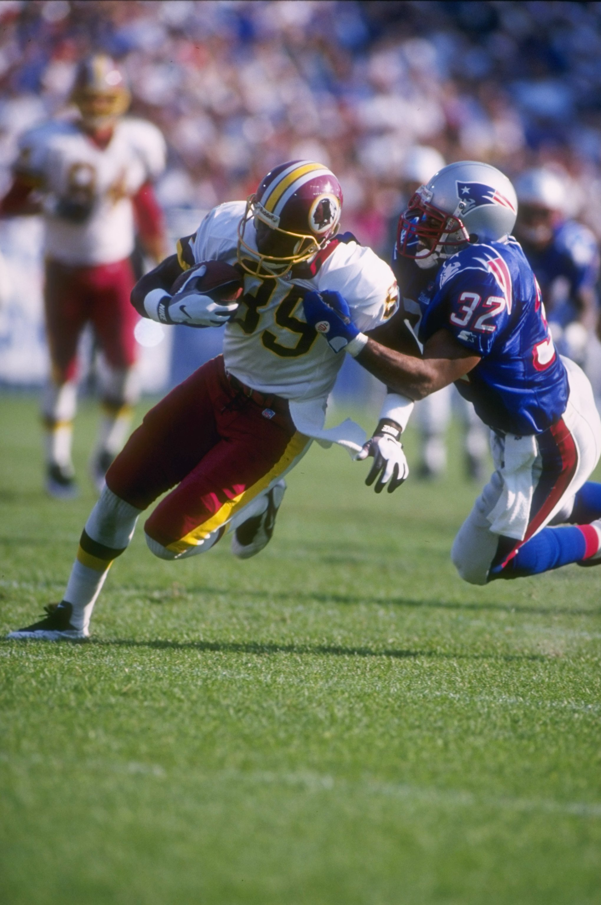 13 Oct 1996: Wide receiver Henry Ellard #89 of the Washington Redskins hangs onto the football as he attempts to run through the diving grasp of defensive back Willie Clay #32 of the New England Patriots following a recetpion in the Redskins 27-22 victory