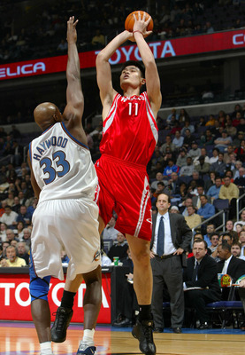 WASHINGTON - JANUARY 13:  Yao Ming #11 of the Houston Rockets shoots over Brendan Haywood #33 of the Washington Wizards during NBA action at the MCI Center on January 13, 2004 in Washington, DC.  NOTE TO USER: User expressly acknowledges and agrees that b