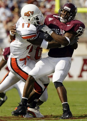 COLLEGE STATION, TX - OCTOBER 25:  Running back Courtney Lewis #25 of the Texas A&M Aggies is tackled by Jon Holland #17 of the Oklahoma State Cowboys at Kyle Field on October 25, 2003 in College Station, Texas.  (Photo by Ronald Martinez/Getty Images)