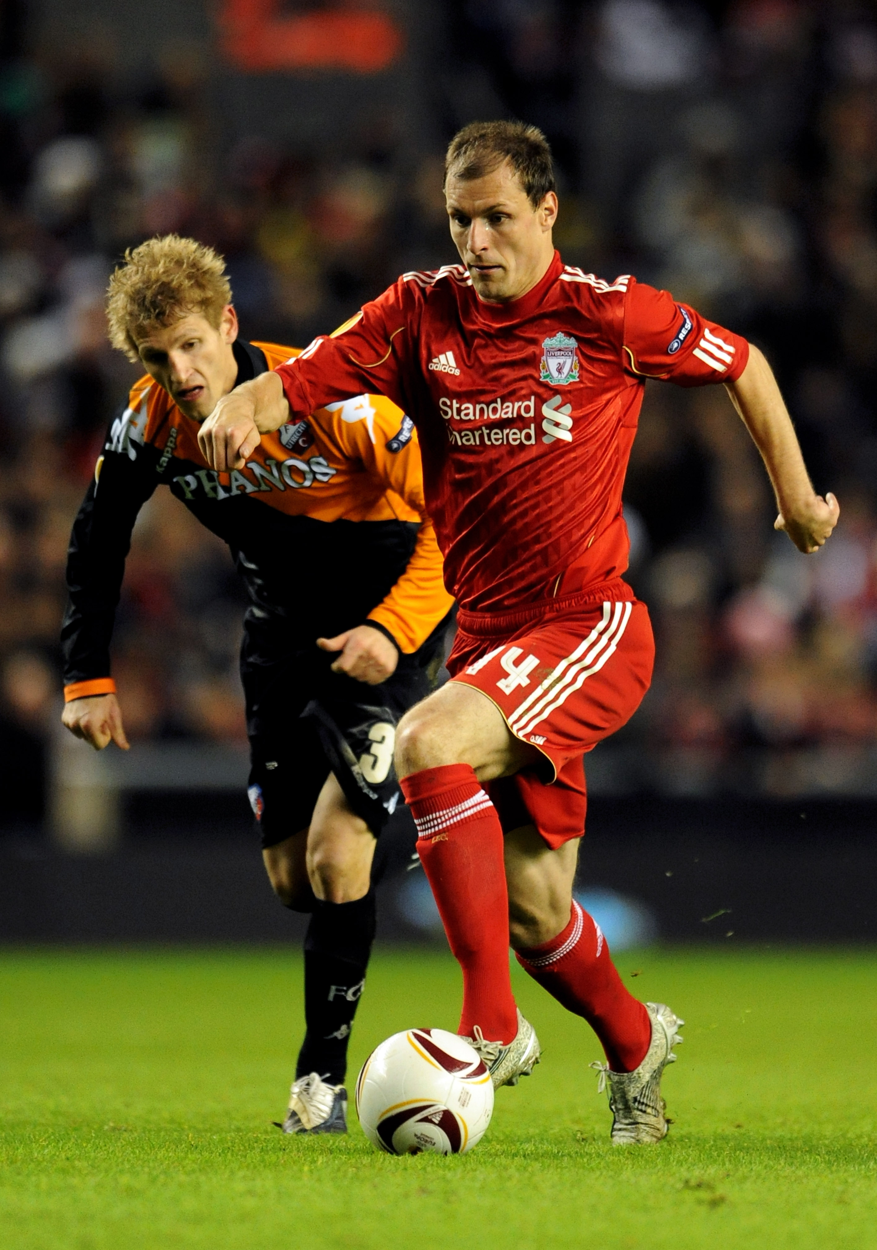 LIVERPOOL, ENGLAND - DECEMBER 15:  Milan Jovanovic of Liverpool is pursued by Mihai Nesu of FC Utrecht during the UEFA Europa League Group K match between Liverpool and FC Utrecht at Anfield on December 15, 2010 in Liverpool, England.  (Photo by Clint Hug