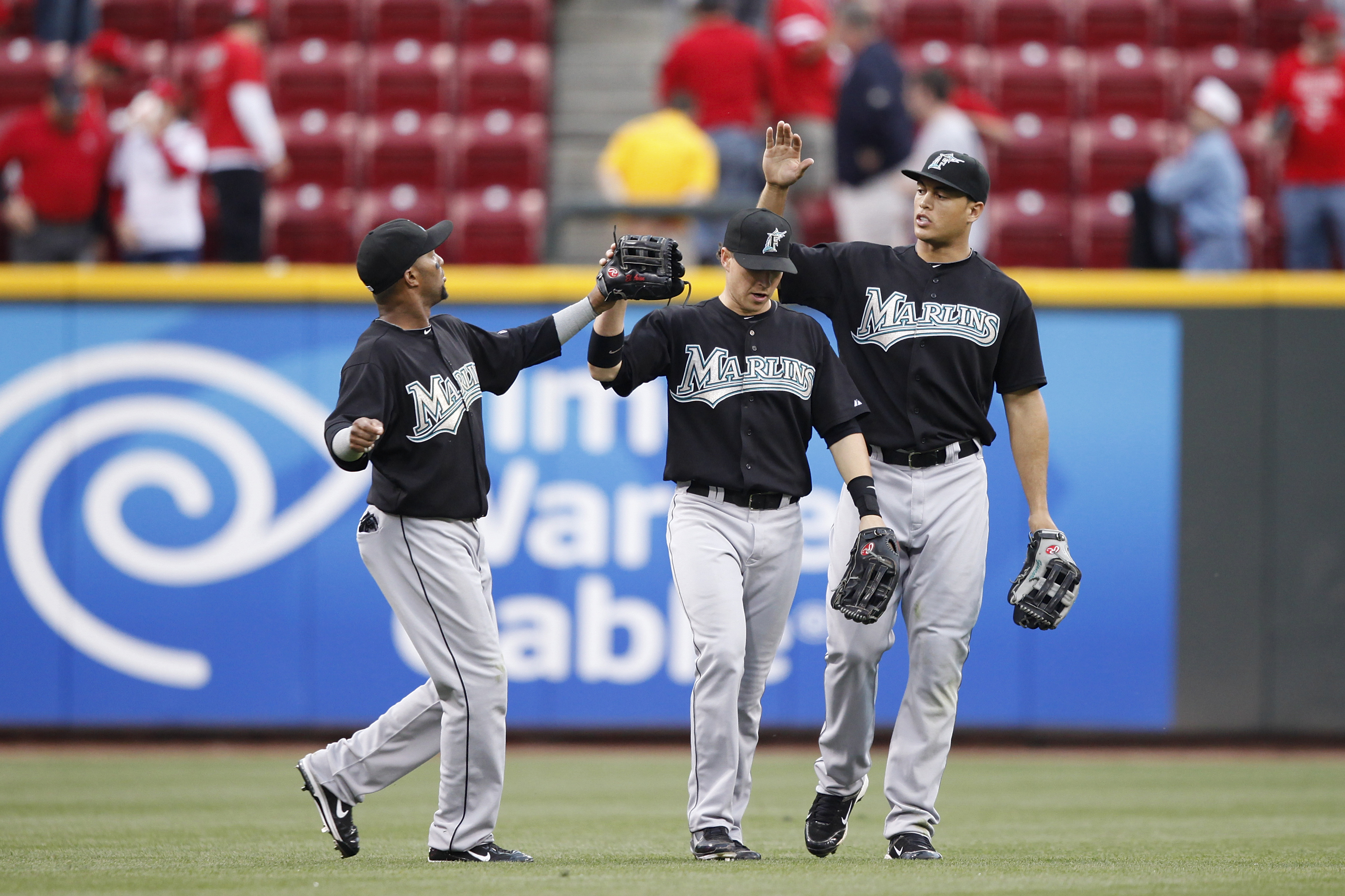 CINCINNATI, OH - MAY 1: Emilio Bonifacio #1, Chris Coghlan #8 and Mike Stanton #27 of the Florida Marlins celebrate after the final out against the Cincinnati Reds at Great American Ball Park on May 1, 2011 in Cincinnati, Ohio. The Marlins defeated the Re