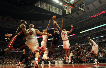 CHICAGO, IL - FEBRUARY 24: Mario Chalmers #15 of the Miami Heat puts up a shot between Derrick Rose #1 and Joakim Noah #13 of the Chicago Bulls at the United Center on February 24, 2011 in Chicago, Illinois. The Bulls defeated the Heat 93-89. NOTE TO USER