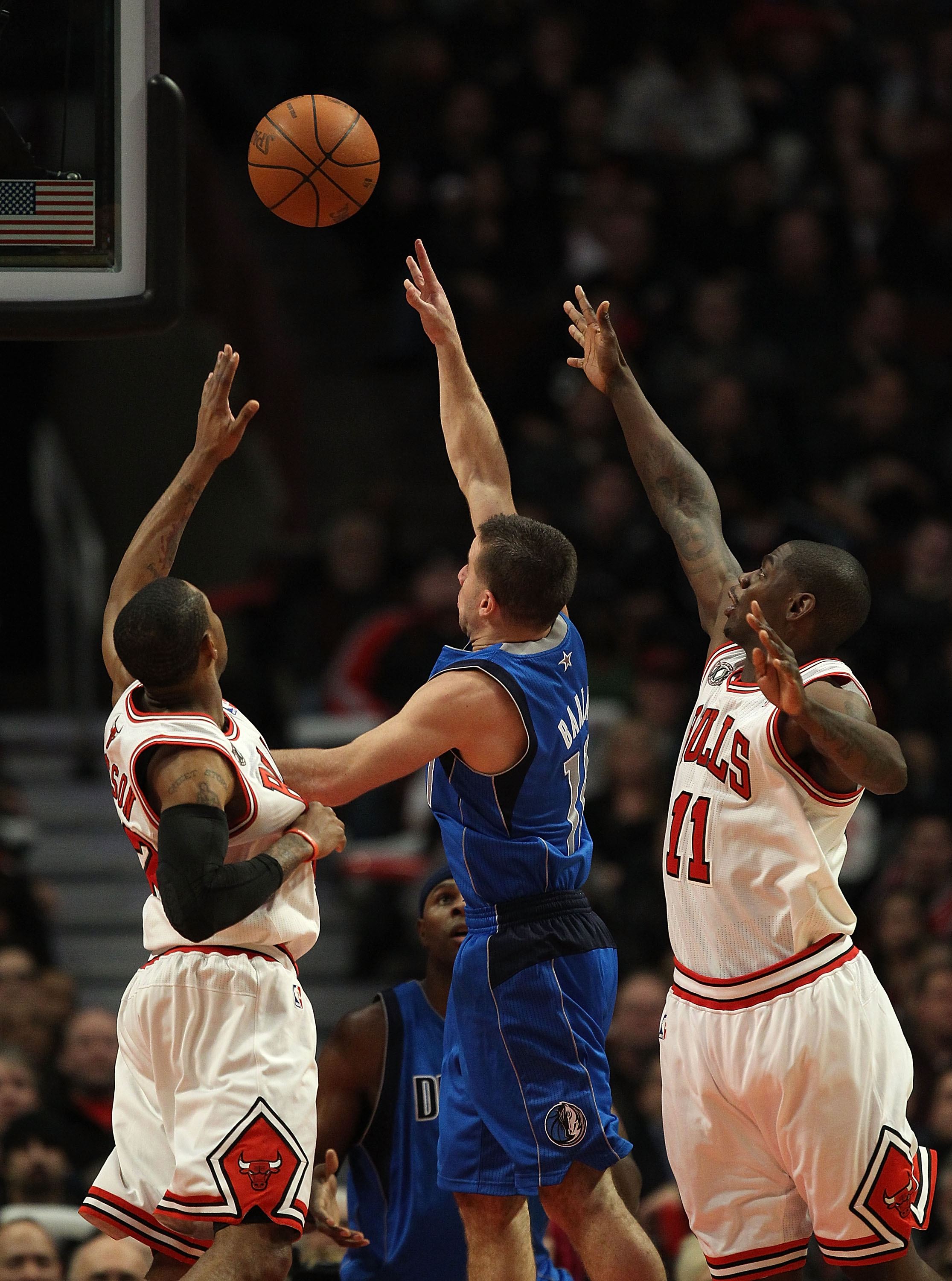 CHICAGO, IL - JANUARY 20: Jose Barera #11 of the Dallas Mavericks goes up for a shot between C.J. Watson #32 and Ronnie Brewer #11 of the Chicago Bulls at the United Center on January 20, 2011 in Chicago, Illinois. The Bulls defeated the Mavericks 82-77.