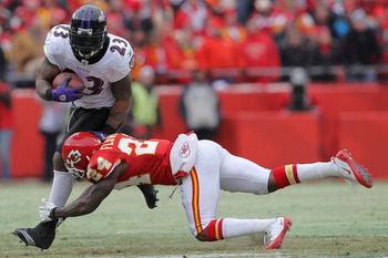 KANSAS CITY, MO - JANUARY 09:  Running back Willis McGahee #23 of the Baltimore Ravens breaks a tackle by cornerback Brandon Flowers #24 of the Kansas City Chiefs in the first half of their 2011 AFC wild card playoff game at Arrowhead Stadium on January 9