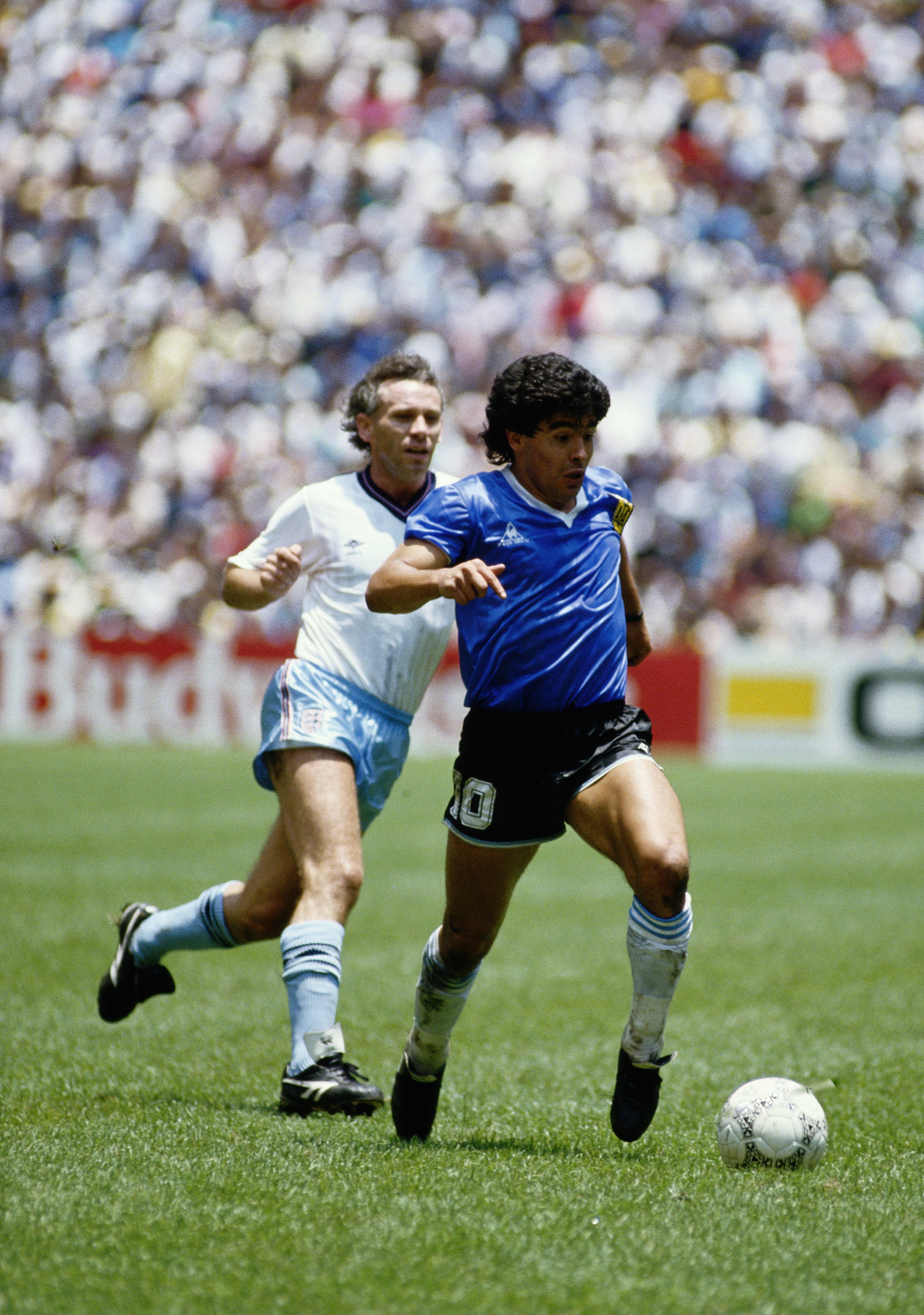 Diego Maradona of Argentina runs with the ball passed Peter Reid of England during the 1986 FIFA World Cup Quarter Final on 22 June 1986 at the Azteca Stadium in Mexico City, Mexico. Argentina defeated England 2-1 in the infamous Hand of God game. (Photo