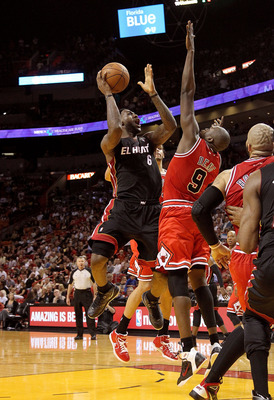 MIAMI, FL - MARCH 06:  LeBron James #6 of the Miami Heat shoots over Luol Deng #9 of the Chicago Bulls during a game at American Airlines Arena on March 6, 2011 in Miami, Florida. NOTE TO USER: User expressly acknowledges and agrees that, by downloading a