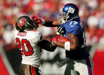 TAMPA, FL - JANUARY 06:  Plaxico Burress #17 of the New York Giants grabs the face mask of Ronde Barber #20 of the Tampa Bay Buccaneers in the fourth quarter of the NFC Wild Card game against Tampa Bay Buccaneers at Raymond James Stadium on January 6, 200