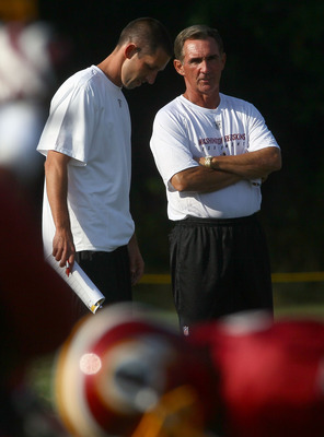 ASHBURN, VA - JULY 30:  Head coach Mike Shanahan (R) of the Washington Redskins speaks with his son and offensive coordinator, Kyle Shanahan (L), during the second day of training camp July 30, 2010 in Ashburn, Virginia.  (Photo by Win McNamee/Getty Image