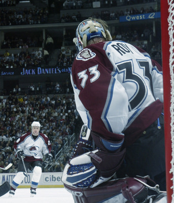 DENVER - APRIL 10:  Darby Hendrickson #14 of the Minnesota Wild takes a shot on goaltender Patrick Roy #33 of the Colorado Avalanche during game one in the first round of the NHL 2003 Stanley Cup playoffs at the Pepsi Center on April 10, 2003 in Denver, C