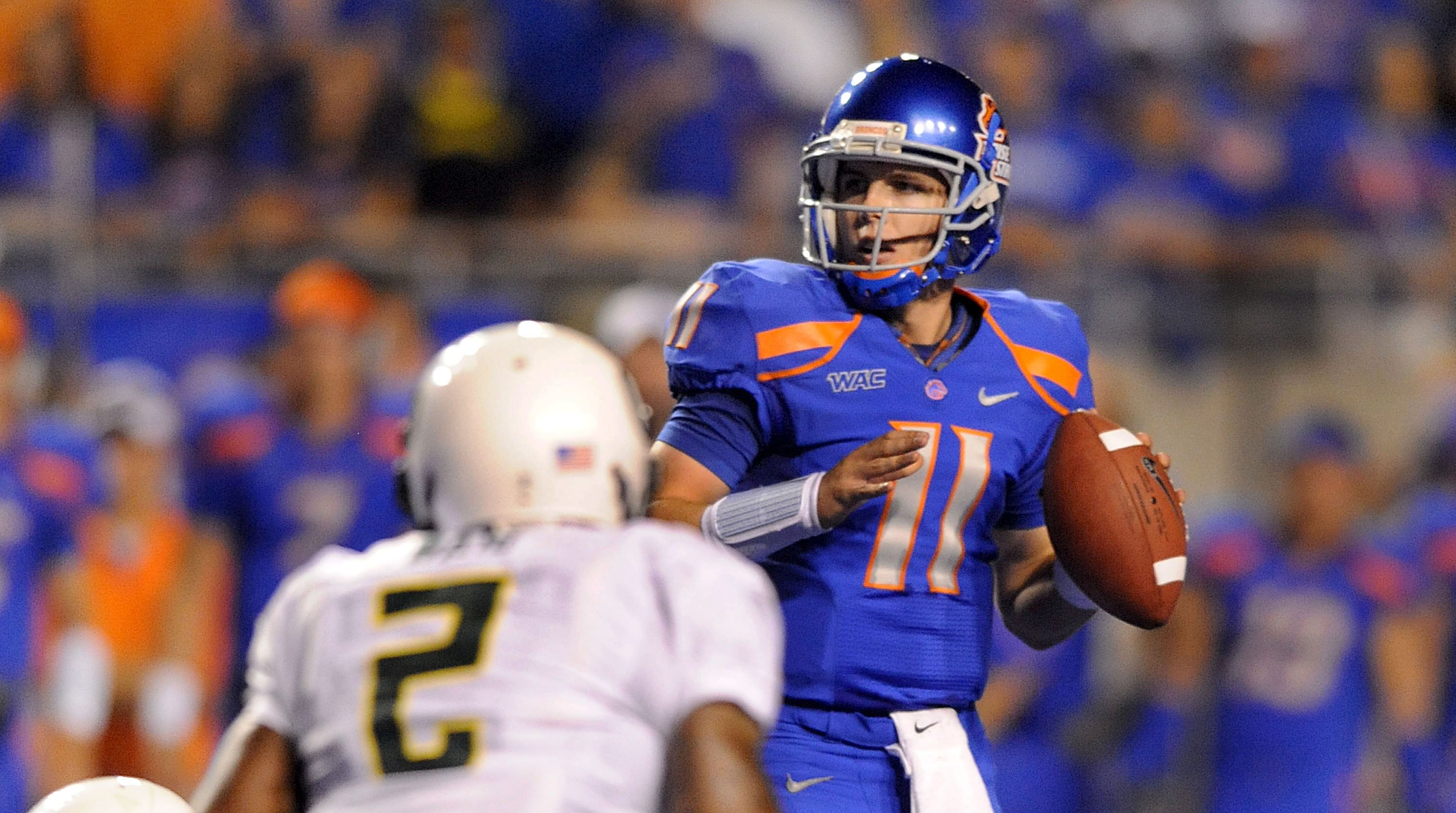 BOISE, ID - SEPTEMBER 3: Quarterback Kellen Moore #6 of the Boise State Broncos looks down field for an open receiver as safety T.J. Ward #2 of the Oregon Ducks applies pressure in the third quarter of the game at Bronco Stadium on September 3, 2009 in Bo