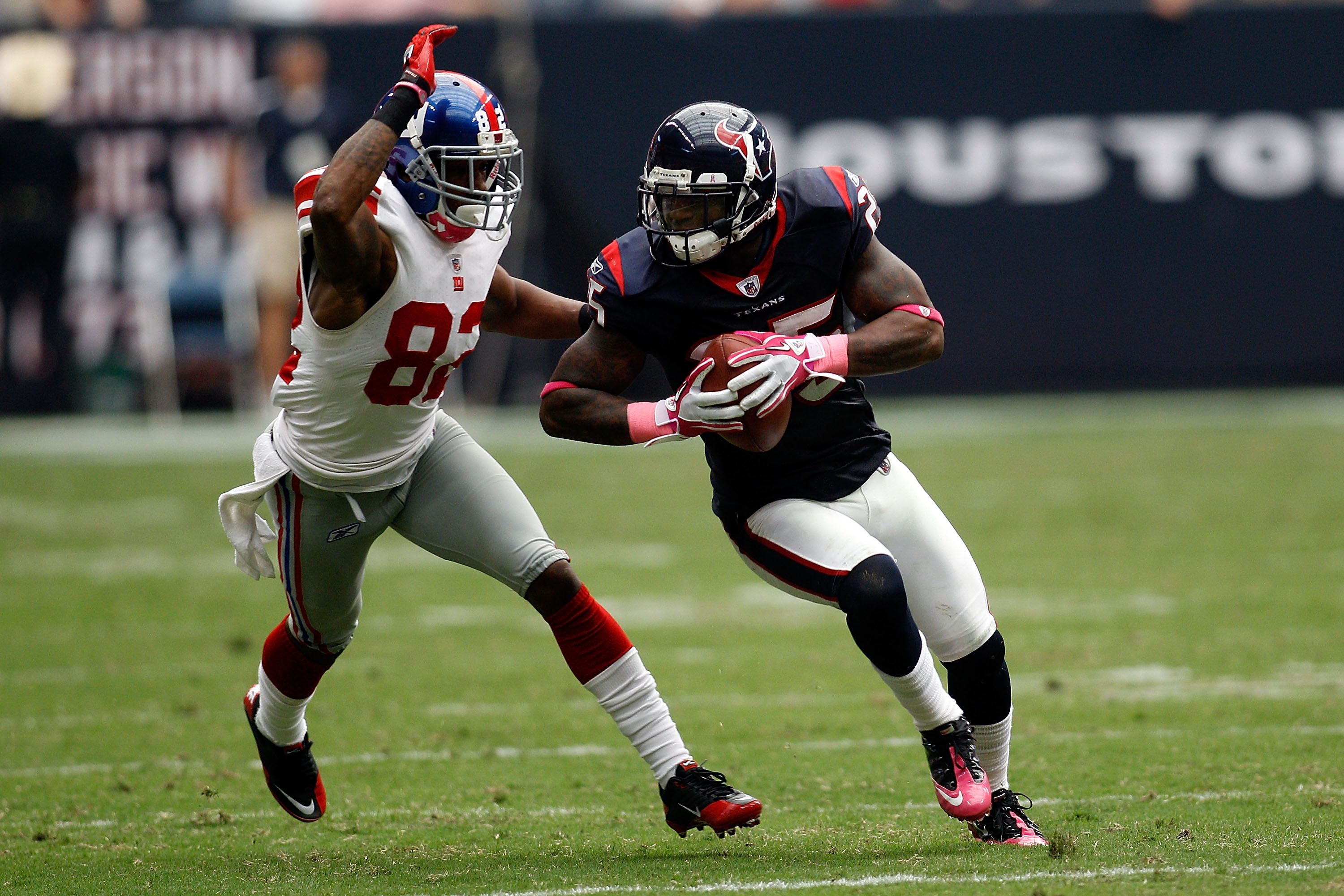 HOUSTON - OCTOBER 10:  Kareem Jackson #25 of the Houston Texans avoids a tackle after intercepting a pass  by Mario Manningham #82 of the New York Giants at Reliant Stadium on October 10, 2010 in Houston, Texas.  The Giants defeated the Texans 34-10.  (Ph