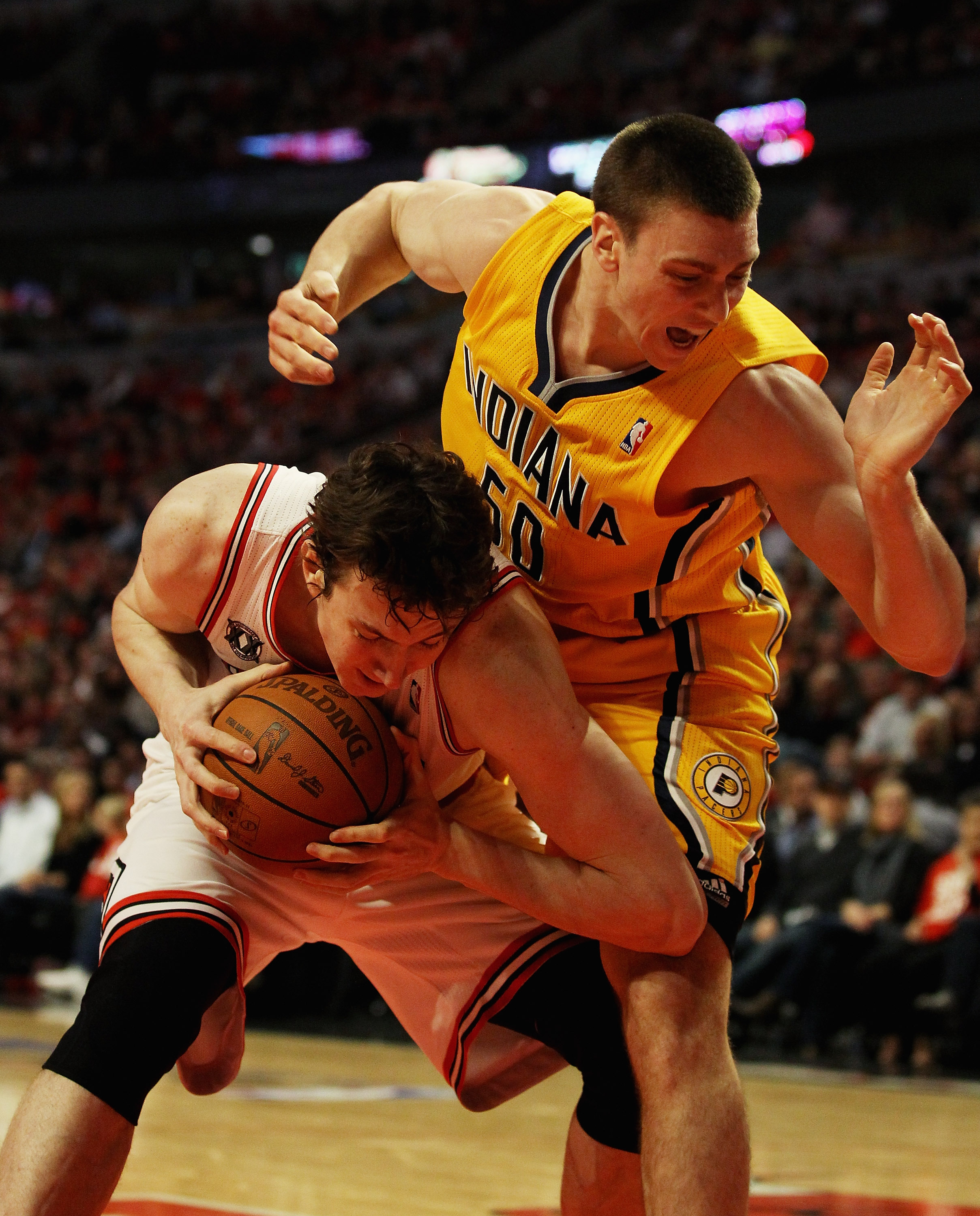 CHICAGO, IL - APRIL 26: Tyler Hansbrough #50 of the Indiana Pacers lands on Omer Asik #3 of the Chicago Bulls after Asik grabbed a rebound in Game Five of the Eastern Conference Quarterfinals in the 2011 NBA Playoffs at the United Center on April 26, 2011