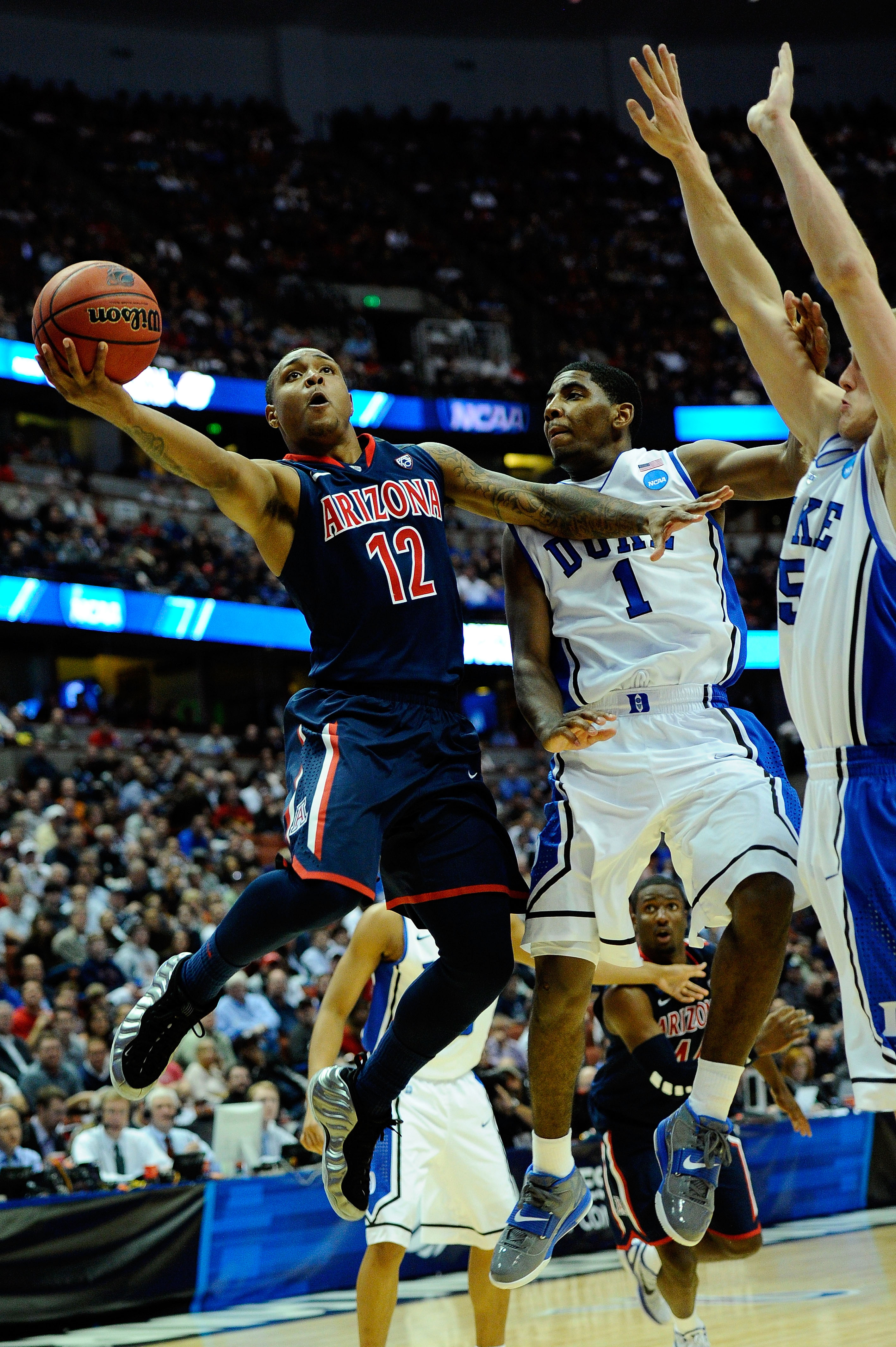 ANAHEIM, CA - MARCH 24:  Lamont Jones #12 of the Arizona Wildcats goes to the hoop against Kyrie Irving #1 and Mason Plumlee #5 of the Duke Blue Devils during the west regional semifinal of the 2011 NCAA men's basketball tournament at the Honda Center on