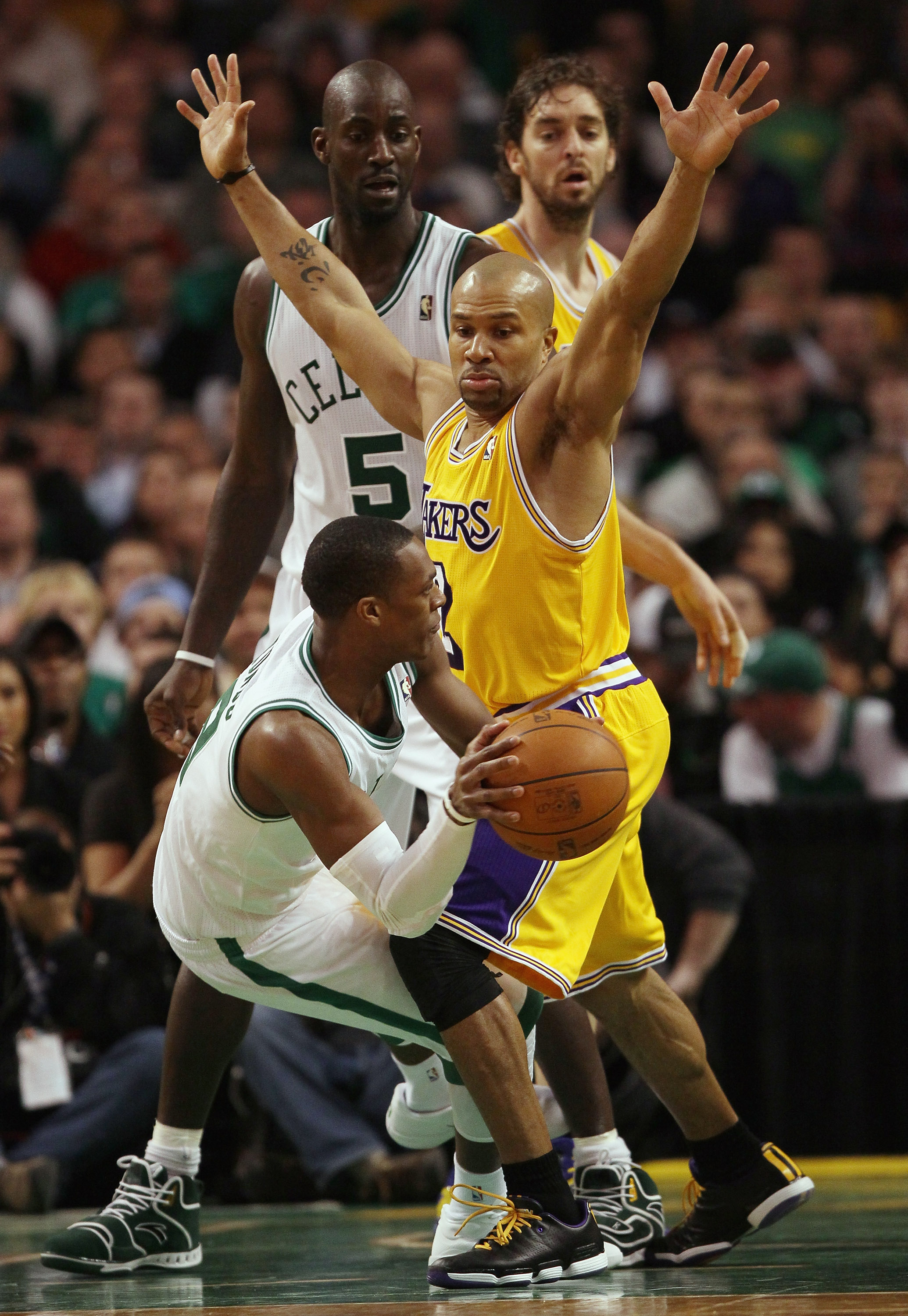 BOSTON, MA - FEBRUARY 10:  Rajon Rondo #9 of the Boston Celtics passes the ball as Derek Fisher #2 of the Los Angeles Lakers defends on February 10, 2011 at the TD Garden in Boston, Massachusetts.  The Lakers defeated the Celtics 92-86. NOTE TO USER: User