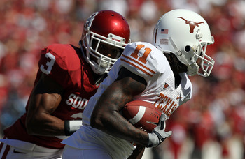 DALLAS - OCTOBER 02:  Wide receiver James Kirkendoll #11 of the Texas Longhorns runs past Jonathan Nelson #3 of the Oklahoma Sooners in the first quarter at the Cotton Bowl on October 2, 2010 in Dallas, Texas.  (Photo by Ronald Martinez/Getty Images)