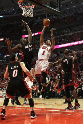 CHICAGO, IL - MAY 15:  Derrick Rose #1 of the Chicago Bulls attempts a shot against Mike Bibby #0, Joel Anthony #50 and Chris Bosh #1 of the Miami Heat in Game One of the Eastern Conference Finals during the 2011 NBA Playoffs on May 15, 2011 at the United