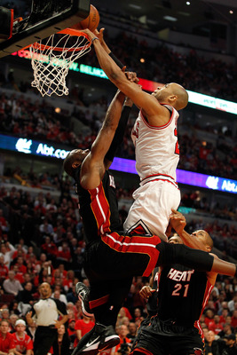 CHICAGO, IL - MAY 15:  Taj Gibson #22 of the Chicago Bulls dunks against Dwyane Wade #3 of the Miami Heat in Game One of the Eastern Conference Finals during the 2011 NBA Playoffs on May 15, 2011 at the United Center in Chicago, Illinois. NOTE TO USER: Us