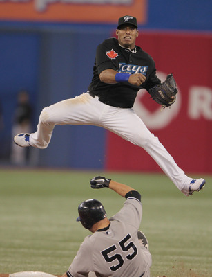 TORONTO, ON - APRIL 20:  Yunel Escobar #5 of the Toronto Blue Jays makes a play at second base on Russell Martin #55 of the New York Yankees during their game at Rogers Centre on April 20, 2011 in Toronto, Canada.  (Photo by Scott Halleran/Getty Images)