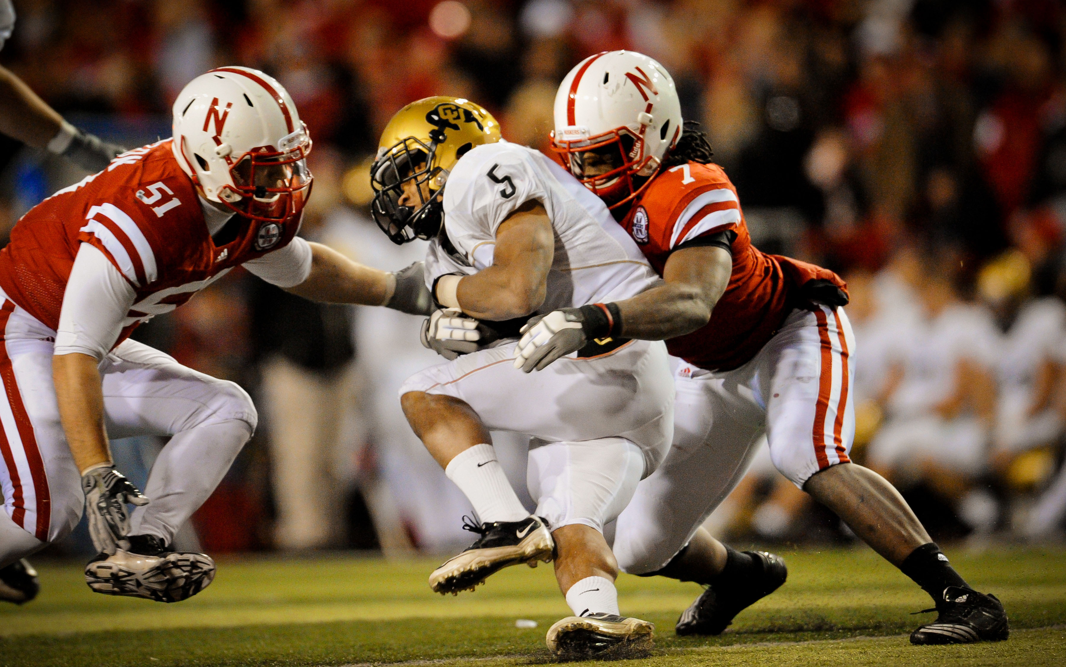 LINCOLN, NE - NOVEMBER 26: DeJon Gomes #7 and Will Compton #51 of the Nebraska Cornhuskers crunch Rodney Stewart #5 of the Colorado Buffaloes during the second half of their game at Memorial Stadium on November 26, 2010 in Lincoln, Nebraska. Nebraska defe