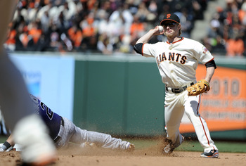 SAN FRANCISCO, CA - MAY 8: Mike Fontenot #14 of the San Francisco Giants gets his throw off to complete the double-play, avoiding the slide of Troy Tulowitzki #2 of the Colorado Rockies during a MLB baseball game at AT&T Park May 8, 2011 in San Francisco,