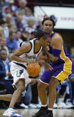 MINNEAPOLIS - MAY 29:  Latrell Sprewell #8 of the Minnesota Timberwolves drives around Rick Fox #17 of the Los Angeles Lakers in Game five of the Western Conference Finals during the 2004 NBA Playoffs at Target Center on May 29, 2004 in Minneapolis, Minne