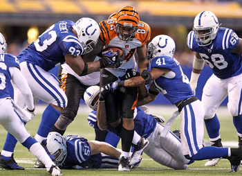 INDIANAPOLIS - NOVEMBER 14:  Jermaine Gresham #84 of the Cincinnati Bengals runs with the ball after catching and is tackled by Dwight Freeney #91 and Antoine Bethea #41 of the Indianapolis Colts in the NFL game at Lucas Oil Stadium on November 14, 2010 i