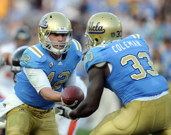 PASADENA, CA - NOVEMBER 06:  Richard Brehaut #12 of the UCLA Bruins handsoff to Derrick Coleman #33 against the Oregon State Beavers at the Rose Bowl on November 6, 2010 in Pasadena, California.  (Photo by Harry How/Getty Images)