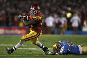PASADENA, CA - DECEMBER 04:  Running back Allen Bradford #21 of the USC Trojans breaks a tackle by Aaron Hester #21 of the UCLA Bruins during the second half at the Rose Bowl on December 4, 2010 in Pasadena, California. USC defeated UCLA 28-14.  (Photo by