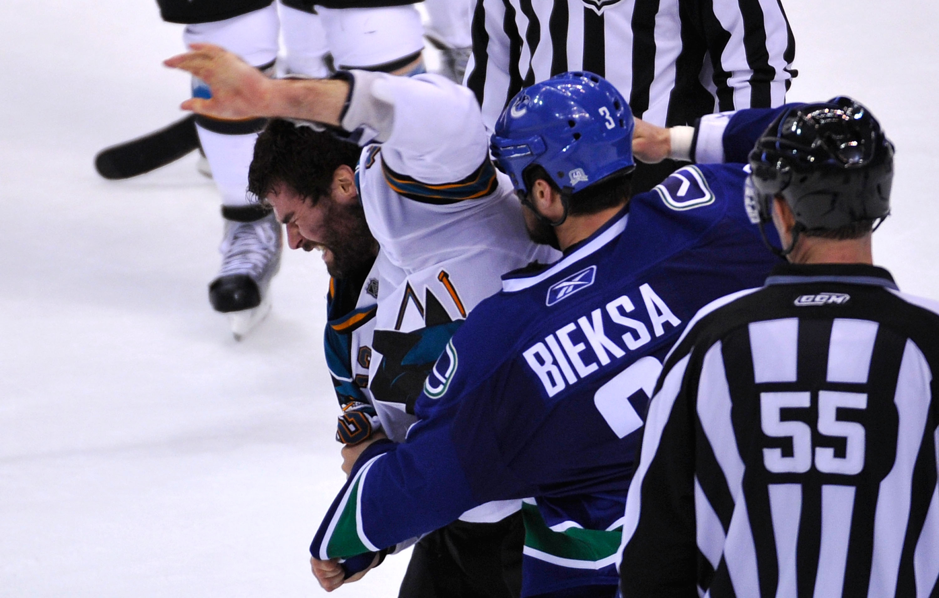 VANCOUVER, CANADA - MAY 18:  Patrick Marleau #12 of the San Jose Sharks tries to defend himself during a fight as Kevin Bieksa #3 of the Vancouver Canucks prepares to throw a punch in the second period in Game Two of the Western Conference Finals during t