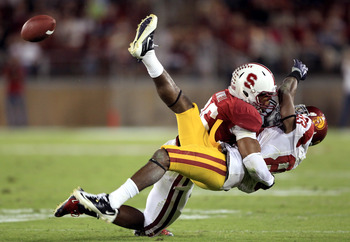 PALO ALTO, CA - OCTOBER 09:  Ronald Johnson #83 of the USC Trojans loses control of the ball when he is hit by Delano Howell #26 of the Stanford Cardinal at Stanford Stadium on October 9, 2010 in Palo Alto, California.  (Photo by Ezra Shaw/Getty Images)