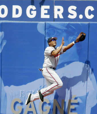 LOS ANGELES  - AUGUST 21:  Outfielder J.D. Drew #7 of the Atlanta Braves and his teammate Andruw Jones #25 attempts to catch the ball against the Los Angeles Dodgers during the game at Dodger Stadium on August 21, 2004 in Los Angeles, California. The Dodg