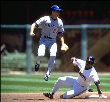 1990: Second baseman Ryne Sandberg of the Chicago Cubs turns a double play as outfielder Kevin Mitchell of the San Francisco Giants slides into second during a 1990 season game at Candlestick Park in San Francisco, California. (Photo by Jonathan Daniel/Ge