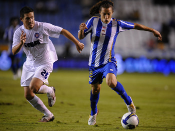 A CORUNA, SPAIN - AUGUST 14: Andres Guardado (R) of Deportivo La Coruna gets past Goran Rubil of Hadjuk Split during the UEFA Cup Second Qualifying Round, first leg match between Deportivo La Coruna and Hadjuk Split at the Riazor stadium on August 14, 200