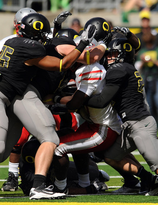 EUGENE, OR - SEPTEMBER 04: Linebacker Casey Matthews #55 of the Oregon Ducks (L) and free safety John Boyett #20 of the Oregon Ducks (R) gang up to tackle running back Demond Dennis #1 of the New Mexico Lobos in the first quarter of the game at Autzen Sta