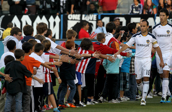 CARSON, CA - MAY 21:  Landon Donovan #10 of the Los Angeles Galaxy greets a line of kids as he leads his team onto the field for ceremonies before the game with Chivas USA at The Home Depot Center on May 21, 2011 in Carson, California.  The Galaxy won 1-0