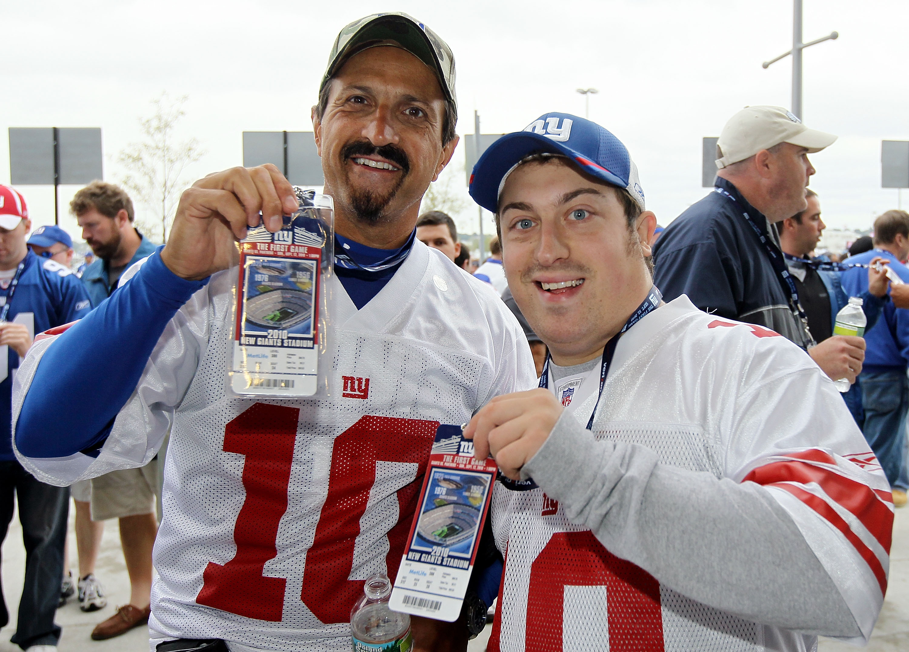 EAST RUTHERFORD, NJ - SEPTEMBER 12:  Jeremy (L) and Christopher Frajetti of New Jersey display their tickets to the first game at the New Meadowlands Stadium between the Carolina Panthers and the New York Giants on September 12, 2010  in East Rutherford,