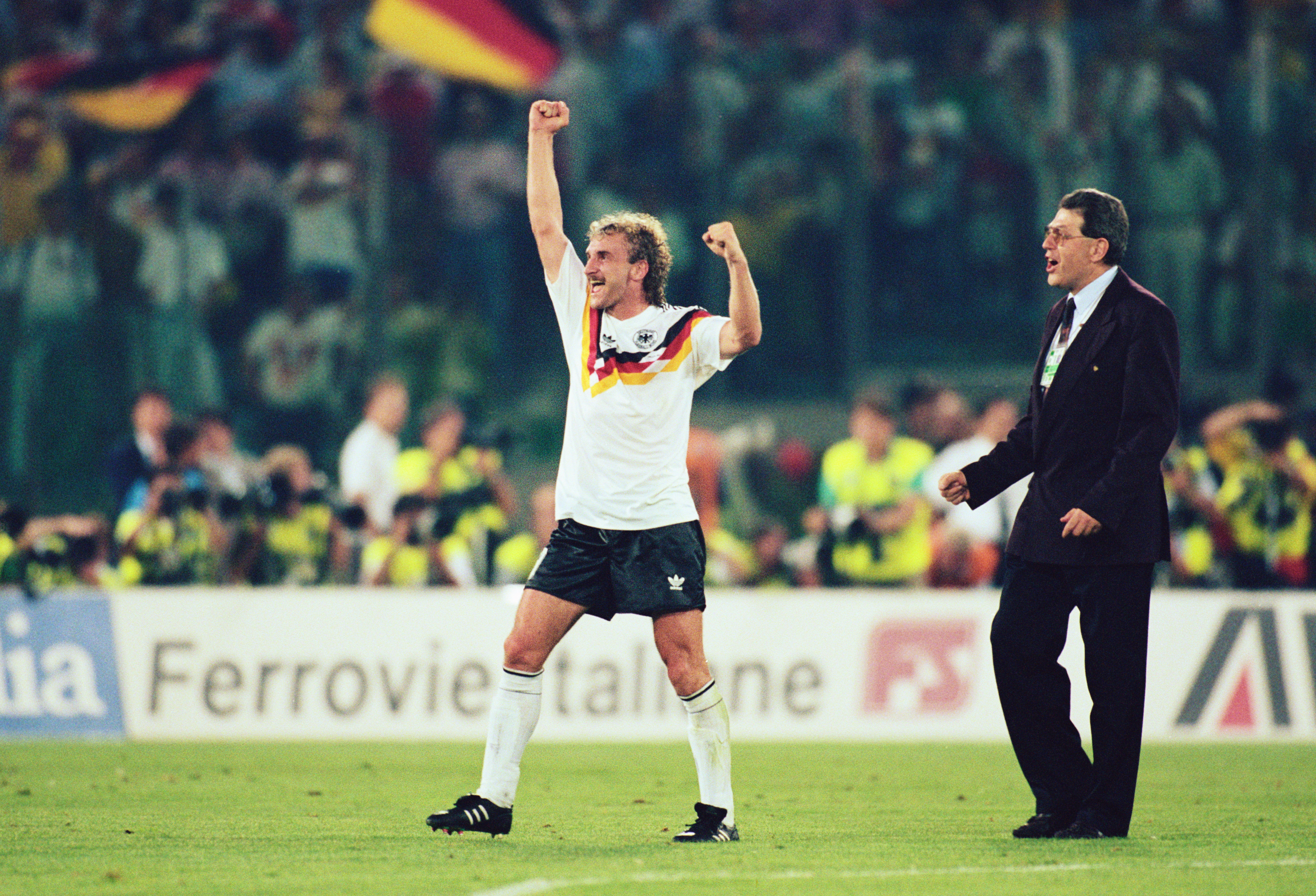 8 JUL 1990:  RUDI VOELLER OF GERMANY WAVES HIS FIST IN CELEBRATION AS GERMAN FLAGS WAVE IN THE CROWD BEHIND HIM AFTER GERMANY WIN THE 1990 SOCCER WORLD CUP FINAL1-0  AGAINST ARGENTINA. Mandatory Credit: Simon Bruty/ALLSPORT