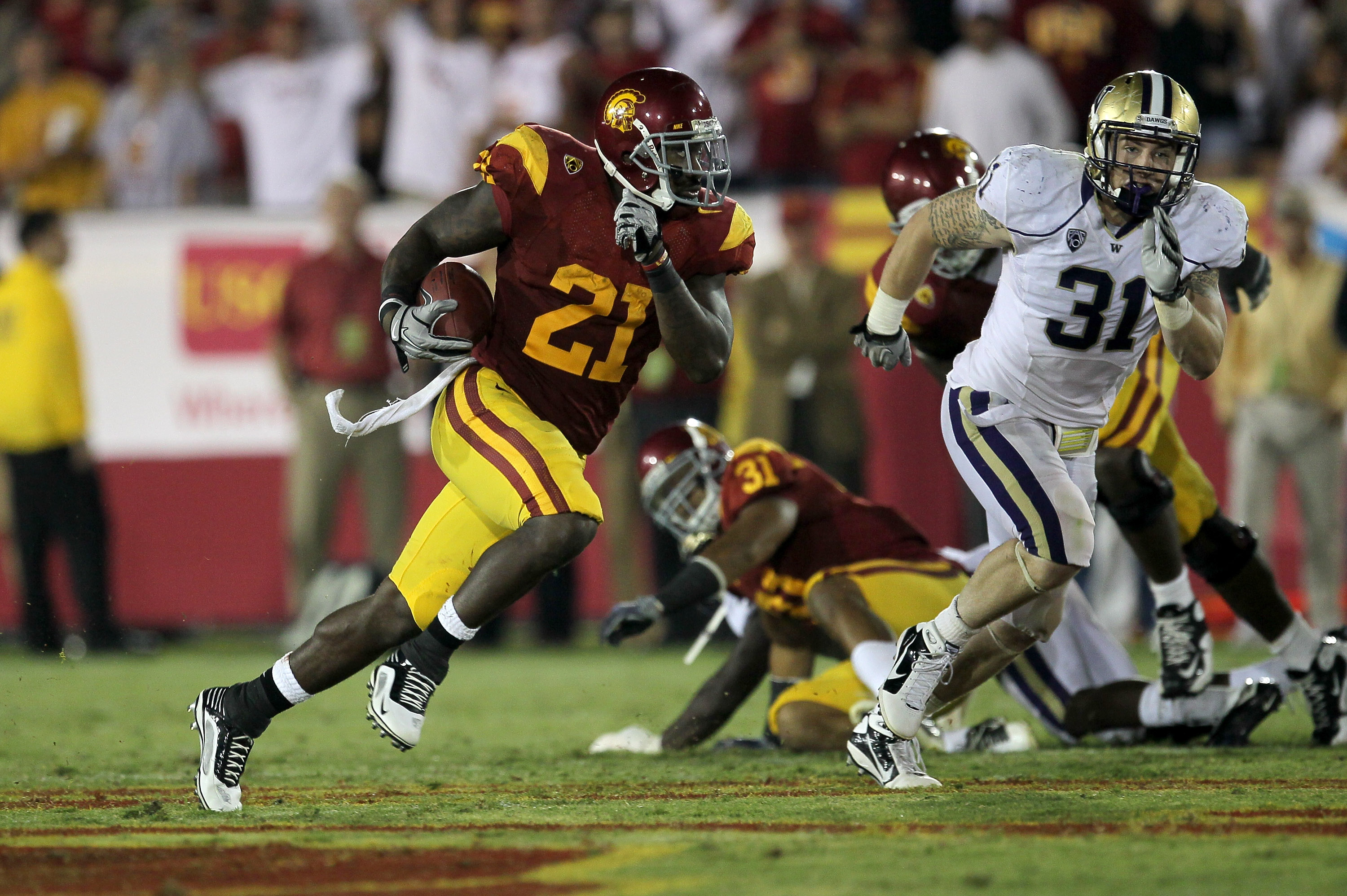 LOS ANGELES, CA - OCTOBER 02:  Running back Allen Bradford #21 of the USC Trojans carries the ball against linebacker Cort Dennison #31 of the Washington Huskies at the Los Angeles Memorial Coliseum on October 2, 2010 in Los Angeles, California.  Washingt